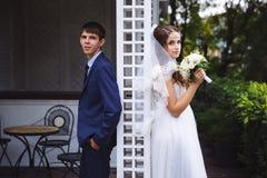 A história de amor, photoshoot do casamento, recém-casados está com suas partes traseiras entre si, a menina cheira um ramalhete  Imagem de Stock