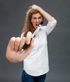 Histeryczna piękna młoda kobieta krzyczy w pokazywać pióro, mieć napad złości Obrazy Stock