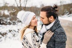 Histoire d'amour de couples de neige d'hiver La belle fille dans le chapeau confortable et l'homme barbu bel s'étreint pull avec Photos stock