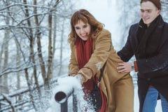 Histoire d'amour en parc d'hiver Jeunes couples gais extérieurs Couples heureux plaing avec la neige fraîche Jour du ` s de Valen Photographie stock libre de droits