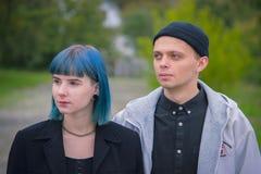 Histoire d'amour gothique de couples Homme et fille bleue de cheveux aux vêtements noirs à la rivière Green Photo stock