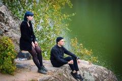 Histoire d'amour gothique de couples Homme et fille bleue de cheveux aux vêtements noirs au fond de la rivière Green Photographie stock