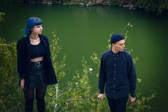 Histoire d'amour gothique de couples Homme et fille bleue de cheveux aux vêtements noirs au fond de la rivière Green Images stock