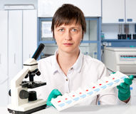 Histopathologist with tissue samples. Histologist with a microscope and a tray of microscopic slides on a white background royalty free stock photos