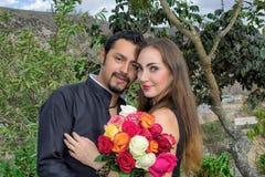 Historia de amor Hombre y mujer que se abrazan en naturaleza en un jardín floreciente Con un ramo de flores imagenes de archivo