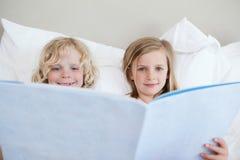 Historia de hora de acostarse de la lectura del hermano y de la hermana Fotografía de archivo libre de regalías
