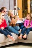 Historia de la lectura de la familia en libro en el sofá en hogar Foto de archivo libre de regalías