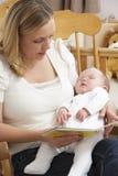 Historia de la lectura de la madre al bebé en cuarto de niños Foto de archivo libre de regalías