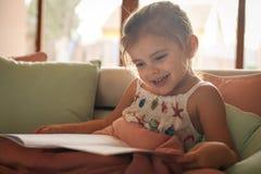 Historia de la lectura de la niña en casa imágenes de archivo libres de regalías