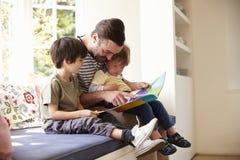Historia de And Sons Reading del padre en casa junto foto de archivo libre de regalías