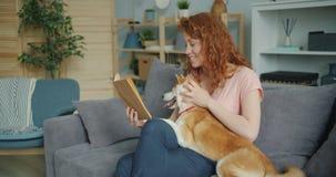 Historia divertida de lectura sonriente de la muchacha y perrito de caricia que se sientan en el sofá en casa almacen de metraje de vídeo