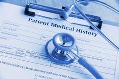 Historial médico paciente en un tablero con el estetoscopio y un bolígrafo azul imagenes de archivo