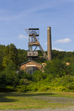 Historic abandoned Landek coal mine tower surrounded by trees Stock Images