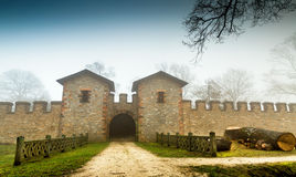 Historic Ancient Castle in a Foggy Misty Day and Wooden Fence. Photo stock photo