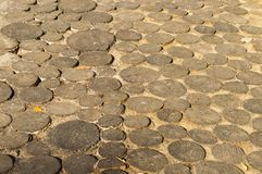 Historic ancient street, paved with cuts of tree trunks. Pedestrian and carriageway. stock photography