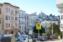 Historic apartments and buildings in San Francisco. Historic homes and buildings on a hilly street in San Francisco, California with the city skyline in the Royalty Free Stock Photos