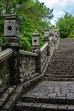 Historic asian handrail with staircase. Historic asian handrail with old stones staircase. Around are trees and partly cloudy sky royalty free stock images