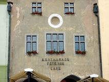 An Austere Prague Restaurant and Cafe Building, Czech Republic. An historic attached building in Old Prague, with an austere stucco facade brightened by red stock photography