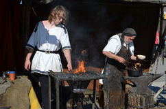 Historic blacksmith at a Middle Ages market. Two blacksmiths in ancient clothing working in their blacksmith's shop at a historic Middle Ages market. Photo taken stock image
