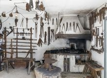 Historic blacksmith workshop with old tools and forge. Pliers, hammer etc stock images