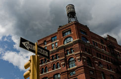 Historic brick building in New York City with water tower on top, stoplight in foreground. Historic brick building in downtown New York City with water tower on royalty free stock image