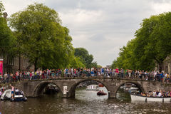 A historic bridge in Amsterdam full of tourists. royalty free stock photography