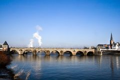 Historic bridge over the river. Historic StServaasbridge over the river Maas in Maastricht, the Netherlands on freezing cold winterday in December Royalty Free Stock Photography