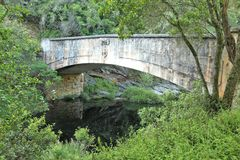 HISTORIC BRIDGE OVER SWART RIVER NEAR GEORGE, WESTERN CAPE. Historic bridge over Swart river crossing the historic seven passes road near George, South Africa stock photo