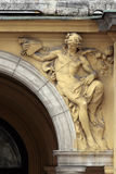 Historic building. Sculpture of naked man on the old building entrance Royalty Free Stock Photo