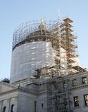 Historic Building Being Renovated. Tall scaffolds stand alongside a government building under heavy renovation stock photography