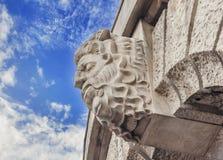 Historic building detail man head with blue cloudy sky Stock Photos