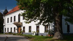 Historic building with flowers in the windows. Driveway to the Manor house with garden in sunny summer day Stock Photos