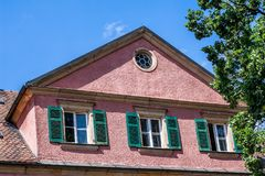 Historic building with lattice windows and green shutters stock photography