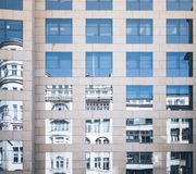 Historic building mirrored in glass facade of modern office building. Old and new contrasting concept Stock Photography