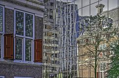 Historic building reflecting in modern facade stock images