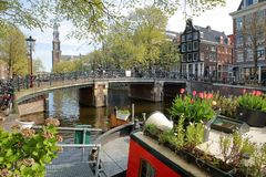 Free Historic Buildings Along Prinsengracht Canal With Westerkerk Church Clock Tower In The Background And Colorful Flowers And Plants Stock Image - 144577571