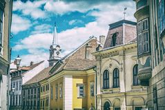 Historic buildings in Sopron, Hungary, analog filter. Historic buildings and church tower in Sopron, Hungary. Architectural theme. Street scene. Analog photo Royalty Free Stock Photos