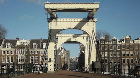 Historic canal houses and elegant bridge in Amsterdam. Historic canal houses and an elegant bridge in Amsterdam, the Netherlands. People are passing by at sunny stock video