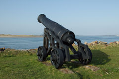 Historic cannon. A black painted historic cannon on wheels positioned overlooking a narrow strait of water Stock Photo