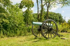 Historic Cannon Artillery. A small historic cannon artillery piece sitting on a slight rise in the ground overlooking a small valley Royalty Free Stock Photography