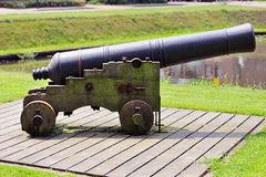 Historic cannon stands ready at the canal Stock Photography