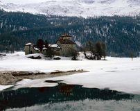A historic castle/building in the snow covered landscape, lake and mountains in the alps Switzerland Stock Photography