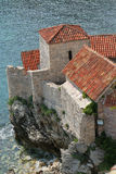 Historic castle by the sea. Historic castle built on rocks  by the sea with gray stone walls, square tower and red pan tiled roof Royalty Free Stock Photos