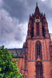 Strasbourg cathedral clock tower. Low angle view of Strasbourg cathedral clock tower under dark cloudscape, France Stock Photography