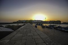 The historic center of `Gallipoli`at sunset. Seen from the pier of the port of the fishing boats stock images