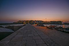 The historic center of `Gallipoli`at sunset. Seen from the pier of the port of the fishing boats stock photo