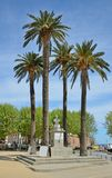 Historic centre of the Corsican town L`Ile Rousse. The bust of Pascal Paoli is surrounded with the palm trees in the main square with a covered market Royalty Free Stock Images