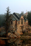 Historic Chapel - vertical. A beautiful stone chapel is built on rocks in the middle of a reflecting pond. This historic chapel, St. Malo Retreat Center, is used Stock Photography