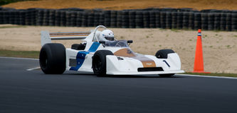 Historic Chevron F1 racing car at speed. Festival of Motorsport: 1977 Chevron Formula 1 race car competing in a Historics Revival Series Stock Images