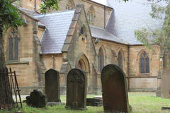 Historic church with churchyard. A churchyard with three old headstones in front of a historic church at a rainy day (in Sydney, Australia&#x29 Stock Images